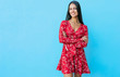 canvas print picture - Best of the best. Full-length photo of an attractive girl in a red dress, posing on a blue background with folded arms, looking in the camera and smiling broadly.