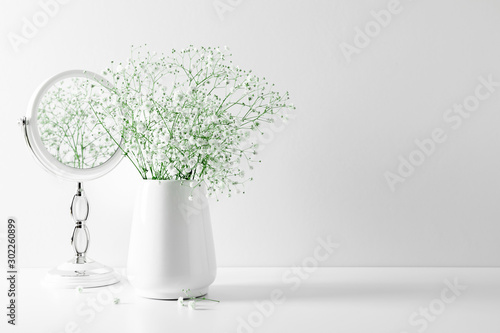 Photo sur Aluminium Fleuriste Elegant floral soft white composition, mirror, white flowers. Beautiful white gypsophila flower in vase on white wall background.