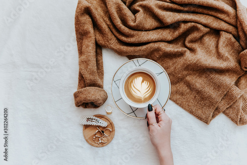Female hands hold latte coffee cup, instagram concept, trendy instagram image. Flat lay, top view