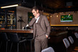 Stylish young man in elegant three-piece suit near bar counter in restaurant interior.