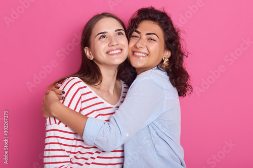 Fotografie, Tablou Two pretty sisters or friends women with dark hair, wearing casual shirts