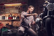 Man Taking Photo Of Motorcycle In Garage