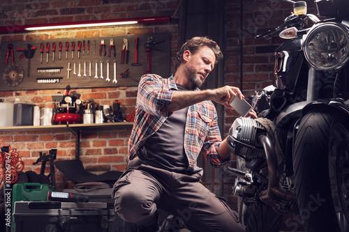 Photo Man taking photo of motorcycle in garage