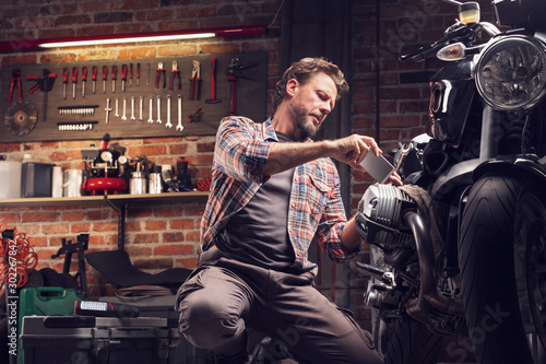 Fototapeta Man taking photo of motorcycle in garage obraz