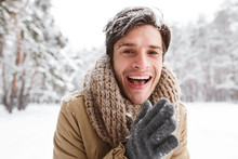 Guy Rubbing Hands To Warm Up Standing In Winter Forest