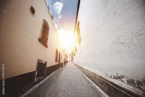 Beautiful shot of an alleyway in the middle of buildings with the sun shining in the background