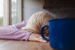 Blonde woman resting her head on a kitchen table, blue cup of coffee in front of her