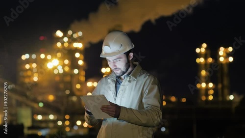 Manager Working on Tablet standing near factory.