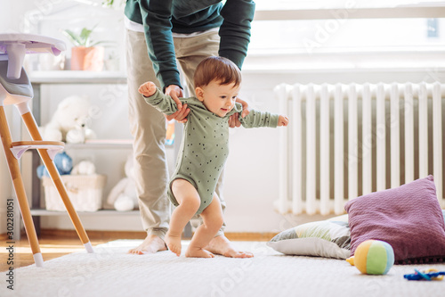 Obraz na plátně Young father helping baby to practice walking, they are home and enjoy in time t