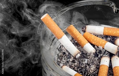 Photo  Ashtray and smoked cigarettes on backgrouund