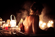 Young Woman In Steamy Outdoor Bath With Partner By Candle Light