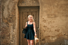Attractive Female Standing By Spotted Door Of Old House