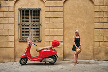 Stylish Female Standing By Red Scooter