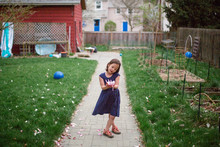 A Little Girl Admires A Large Pink Flower In Her Hands