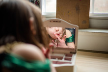 A Little Girl Looks At Her Reflection In A Jewelry Box Mirror