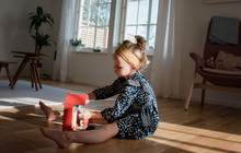 Young Girl Playing With Pretend Coffee Set At Home In Window Light
