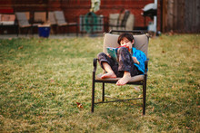 A Happy Boy Reads A Book Barefoot In Backyard In Cool Weather