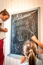 Two Girls Drawing On Blackboard