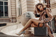 Autumn Fashion Concept: Young Elegant Woman Wearing Beige Trench Coat, Heels, Posing With Classic Black Tweed Bag, Handbag. Copy, Empty Space For Text. Outdoor Full-length Portrait