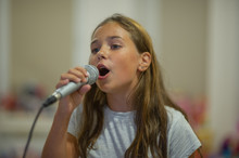 Young Girl With Microphone On ...