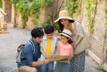 Young Chinese Family Looking At Map Outdoors