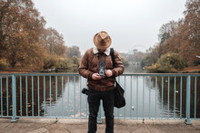 Adult Man In Hat Using Retro Photo Camera While Standing On Bridge Over Calm River In Autumn Park In London