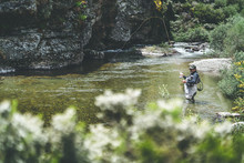 Side View Of Equipped Man Harling Fish While Standing In Waders In Mountain Torrent By Cliff And Forest