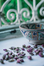 Small Dried Flower Buds And Ornamental Bowl Placed Near Open Window Inside Traditional Arabic Home In Marrakesh, Morocco