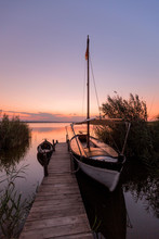 Moored Boat By Wooden Pier
