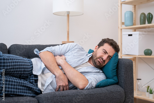 Man lying on the sofa feeling pain and stomachache Canvas Print