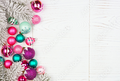 Autocollant pour porte Roses Christmas side border with pink, purple and teal ornaments and tree branches. Above view on a white wood background.