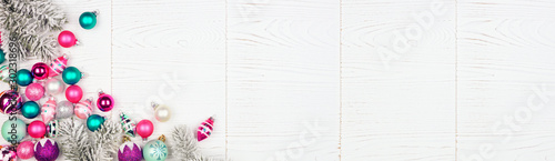 Christmas corner border banner with pink, purple and teal baubles and tree branches. Above view on a white wood background.