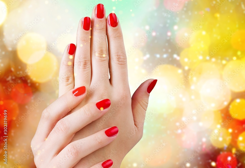 Fototapeta Young beautiful woman hands with red manicure