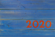 Year 2020 In Bold Red Hanging On Rustic Blue Wood Background