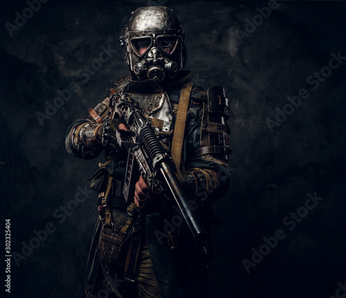 Cool cosplay costume of post - apocalypse knight, man is posing at dark photo studio. Wall mural