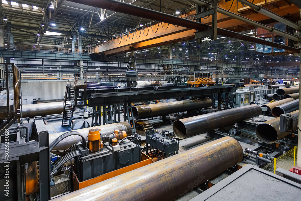 Fototapeta Pipe factory production line, unfinished pipe moving on roller conveyor