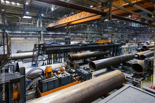 Fotografía  Pipe factory production line, unfinished pipe moving on roller conveyor