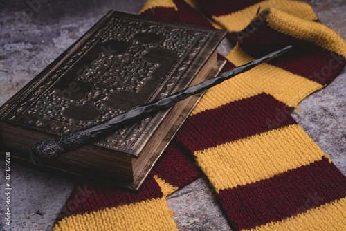 Subjects of the school of magic. Scarf, magic wand, book of spells on grey stone background.