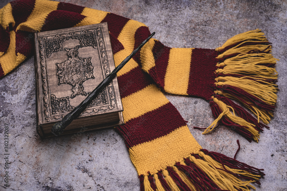 Fototapeta Subjects of the school of magic. Scarf, magic wand, book of spells on grey stone background.