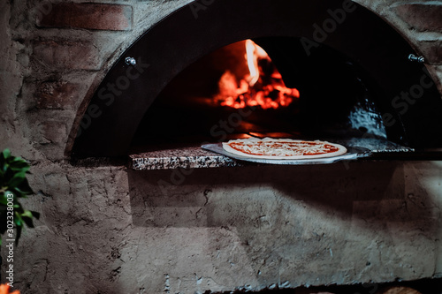 Italian chef is putting prepared margarita pizza to the oven with flame in it Canvas Print