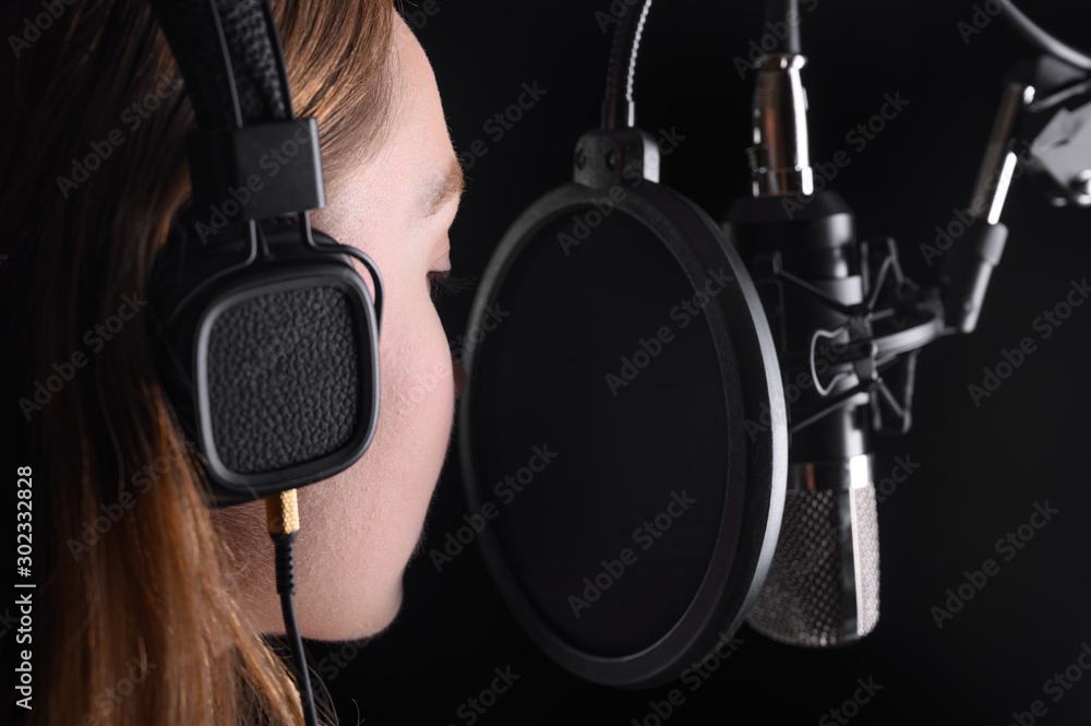 Fototapety, obrazy: Female vocal recording. Young girl with microphone and headphones in recording studio. Recording of vocal, blogger, reading text, voice acting.