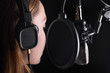 Leinwandbild Motiv Female vocal recording. Young girl with microphone and headphones in recording studio. Recording of vocal, blogger, reading text, voice acting.
