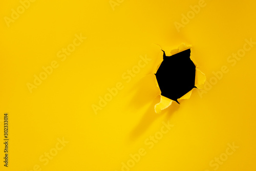 Fotografia Torn hole in yellow paper background.