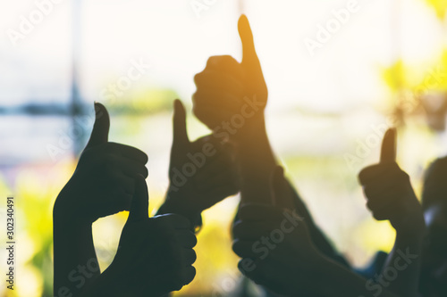 Obraz Silhouette image of many people's hands making thumb up sign - fototapety do salonu