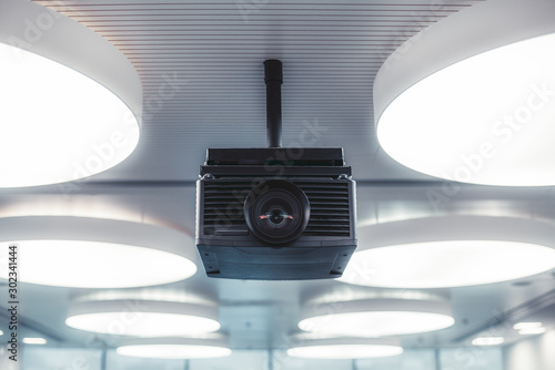 Valokuva  A black modern projector with a plastic case and a huge lens with aberrations in