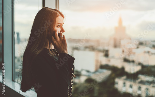 Valokuva  Sideview of an adult beautiful caucasian businesswoman talking on the phone whil