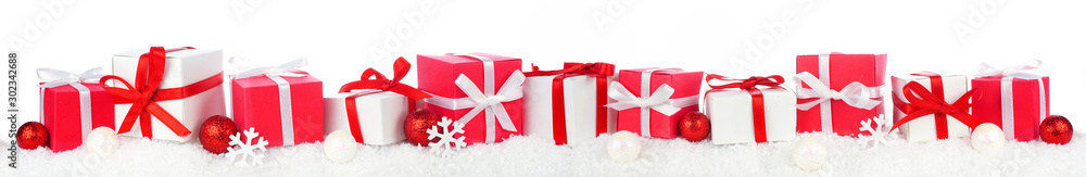 Fototapeta Christmas border of red and white gift boxes in snow. Side view isolated on a white background.