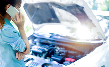 Business Women Have Car Problems On The Side Of The Road.The Light Is Golden At Sunset. Young Women Calling Car Mechanic. Concept Of Quality Inspection Of Cars Engine Maintenance All The Time.