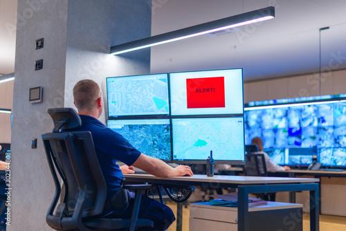 Fototapeta Male computer operator monitoring from a security ( computer, logistic ) center. obraz na płótnie