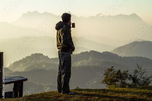 Foto auf Gartenposter Beige a man holding coffee cup on mountain